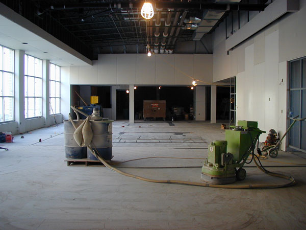 Work continues on the floor of the cafeteria area. The kitchen and serving area is straight ahead while the gymnasium is on the right side (the west end of the school).