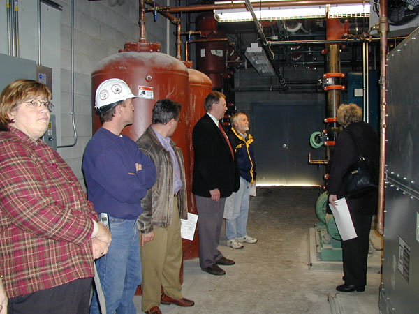School Board members and administrators tour a mechanical room at S.G. Reinertsen Elementary School.
